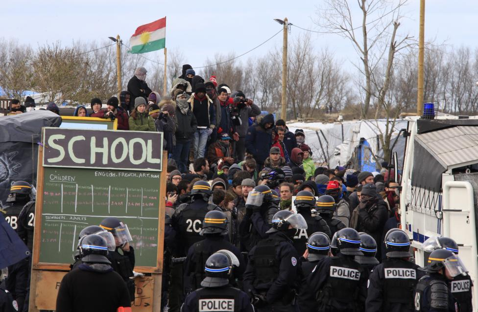 "French riot police face off with migrants and their supporters outside a makeshift school during the partial dismantlement of the camp for migrants called the ""jungle"", in Calais. REUTERS/Pascal Rossignol"