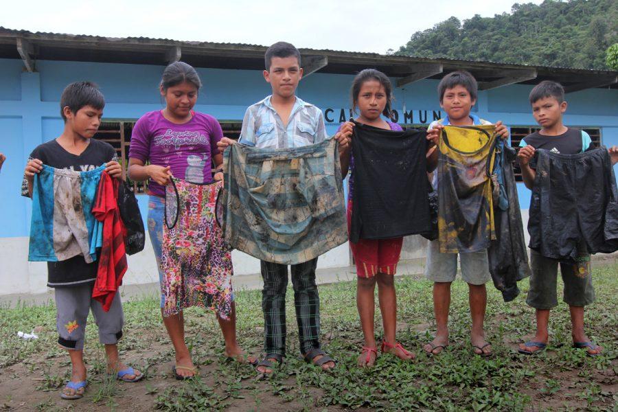Nazareth, un villaggio tra i fiumi di Chiriaco e Maranon. I bambini mostrano i vestiti che indossavano quando sono dovuti andare a scavare il petrolio fuori dal fiume. Foto: Barbara Fraser